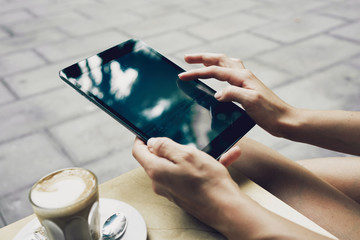 Close up to view young woman's hands hold tablet with empty screen. woman writing email during the coffee break