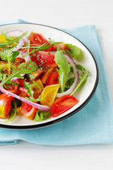 tomato salad with arugula in vintage plate
