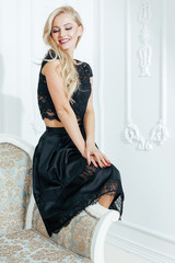 stylish elegant blonde woman in beauty rich interior, wearing black dress smiling