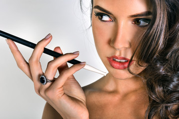 Portrait of beautiful brunette smoking cigarette with long holder
