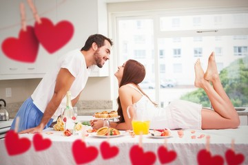 Composite image of young couple having a romantic breakfast
