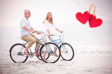 Composite image of happy couple cycling together