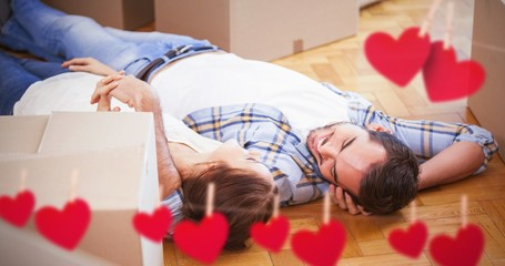 Composite image of cute couple lying on the floor