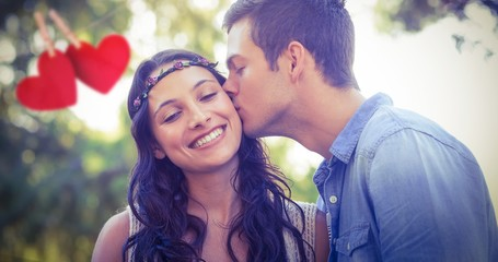 Composite image of cute couple kissing in the park