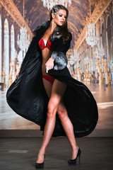 Elegant young woman in seductive red lingerie and luxury fur coat posing in front of wallpaper background.