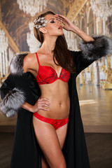 Sexy glamour young woman in red fashionable lingerie and luxury fur coat  posing in an interior.