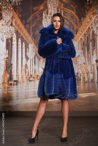 Fashion photo of beautiful young lady in a luxurious fur coat posing  against wallpaper background. 3074d2a8b