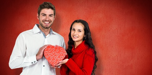 Composite image of couple holding heart shaped gift box