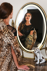 Sexy young woman in a beautiful black lingerie and luxury fur coat stands before the mirror.