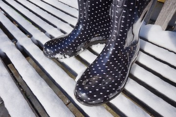 Black winter boots with white polka dots in the snow