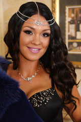 Portrait of attractive brunewtte woman smiling to the camera and wearing jewelery, lingerie and furs