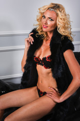 Fashion interior photo of gorgeous woman with blond curly hair wears luxurious lingerie and fur coat.