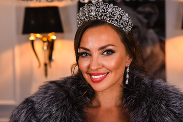 Portrait of Miss Russian Universe 2015 contest winner Yulia Krutova in fur coat wearing tiara.