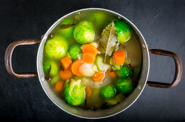 Brussels sprouts soup in a pot on black wooden table