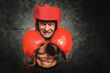 Composite image of angry boxer with gloves and headgear