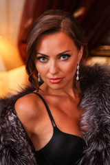 Close up fashion portrait of stunning brunette woman with beautiful  evening makeup and elegant hairstyle wearing fashionable black lingerie and luxury fur coat. Boudoir style.