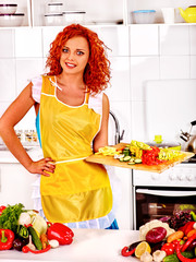Woman with red hair cooking dinner at kitchen at home.