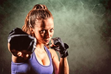 Composite image of portrait of female fighter punching