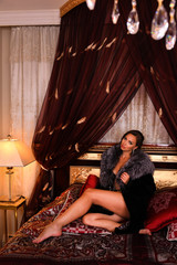 Sexy brunette woman with perfect skin, big full lips posing at luxury  bedroom, wearing stylish black lingerie and fur coat.
