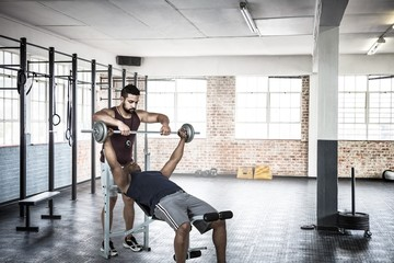 Trainer helping muscular man to lift the dumbell
