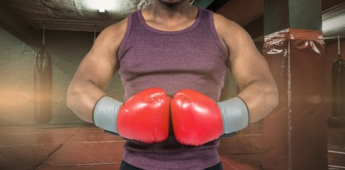 Composite image of fit man with boxing gloves