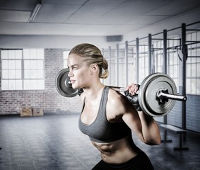 Composite image of muscular woman lifting heavy barbell