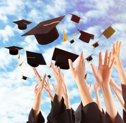 Graduates hands throwing graduation hats in the sky