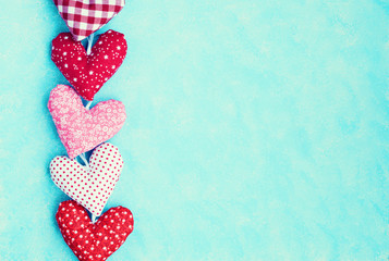 Five vintage stuffed hearts over blue background