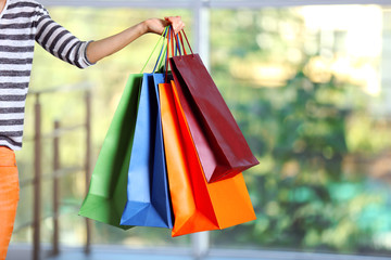 Female hand holding shopping bags on defocused background