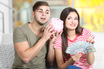 Happy couple with money from the moneybox