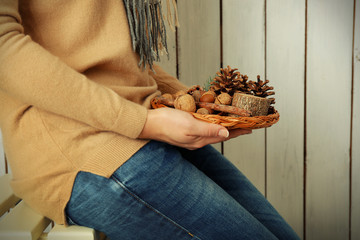 Woman holding wicker basket with nuts and evergreen