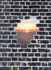 Opening in a brick wall, sunset on sea