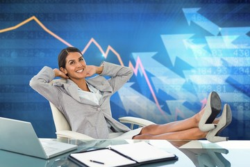 Composite image of businesswoman relaxing in a swivel chair
