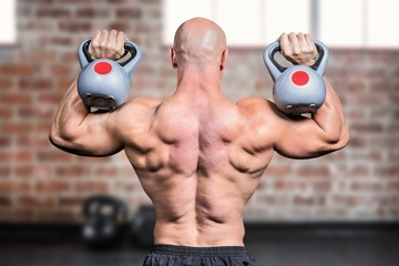 Composite image of rear view of bald man lifting kettlebells