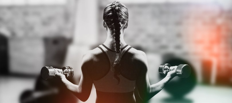 Braided hair woman lifting dumbbell