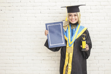 Happy graduated female student wearing graduation gown holds a d