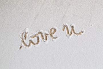 Winter day and love you handwritten words letter on orange color snowy floor.