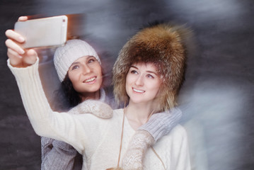 Two smiling girls in winter fur hats.