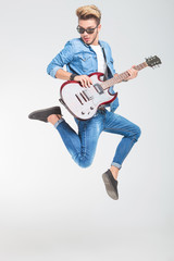rocker jumping one side in studio while playing guitar