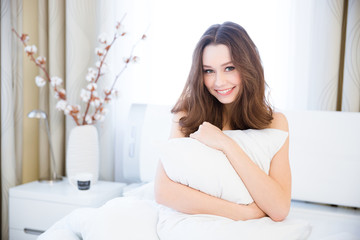 Sensual woman sitting on bed and hugging pillow