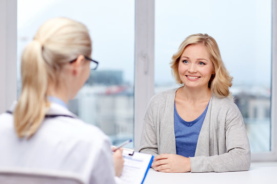 smiling doctor and woman meeting at hospital