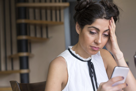 Portrait of young sad woman annoyed by something, receiving bad sms ,