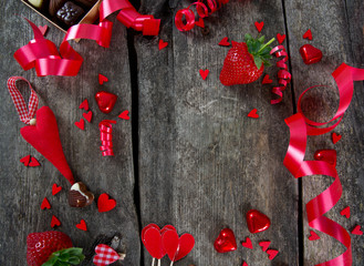 hearts, chocolate, flowers and ribbons on wooden surface