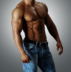 Красивый торс мускулистого мужчины в голубых джинсах.
