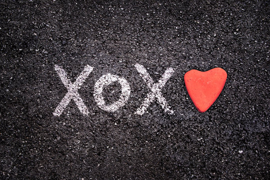 Happy Valentines day card, xoxo on the ground and stone in the shape of a heart