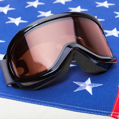 Close up shoot of winter sports implements over USA flag - snowboard or ski goggle
