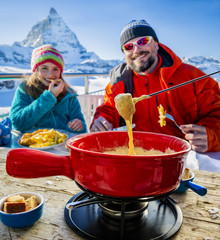 Skiers in a restaurant, Fondue, traditional Swiss dish - Matterhorn in Swiss Alps in background