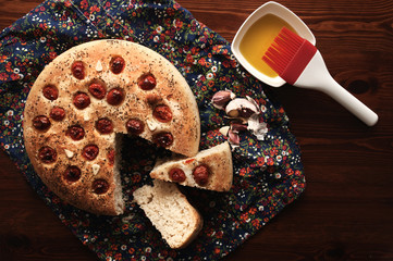 Focaccia (a flat oven-baked Italian bread product) with cherry tomatoes, garlic and oregano