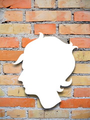 Close-up of a young woman profile silhouette on orange brick wall background