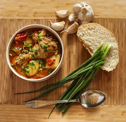 Food - Chicken soup with potatoes and tomatoes, garlic, onion, bread - wood background